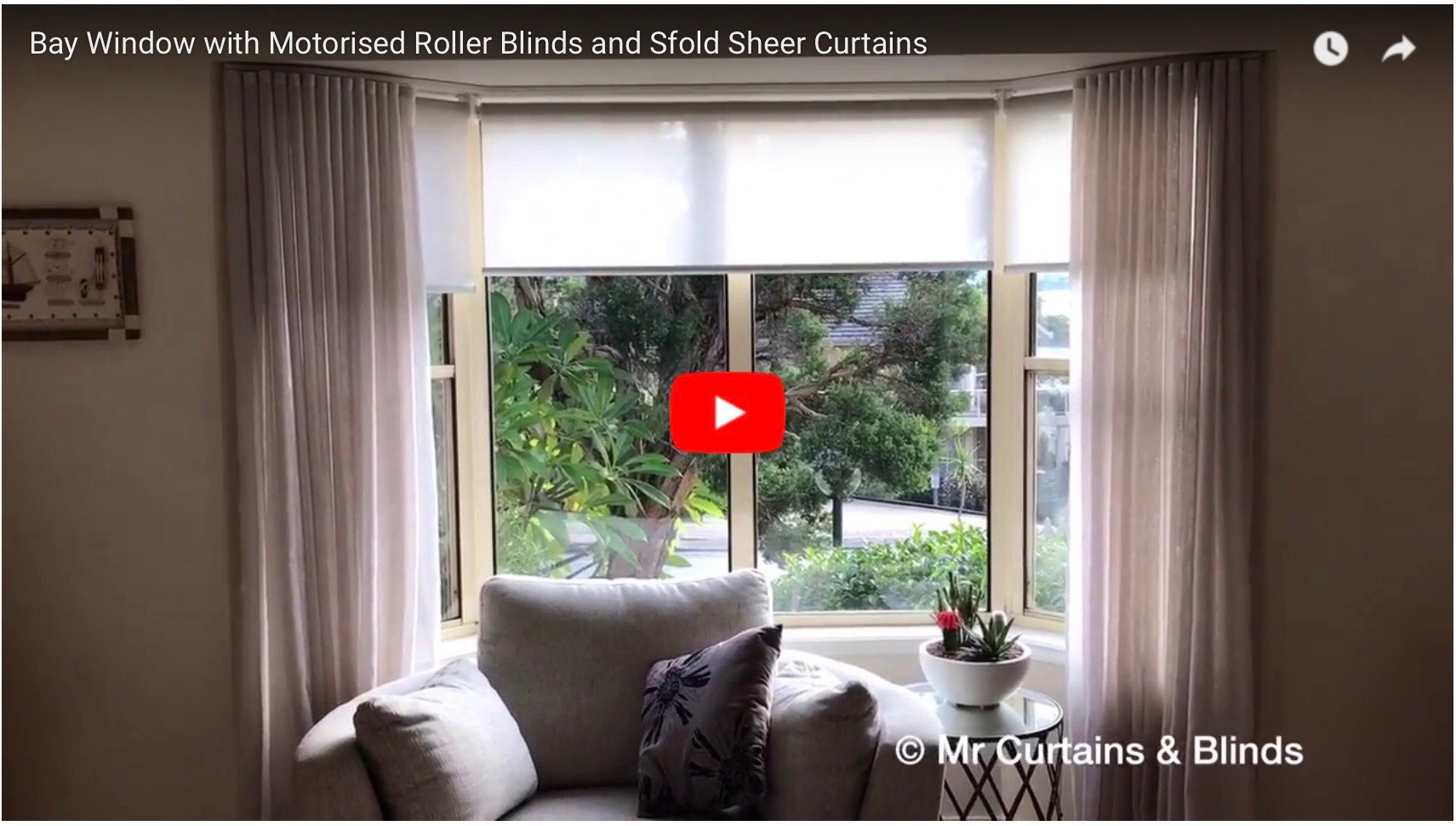 Motorised roller blinds in a bay window with sfold sheer curtains